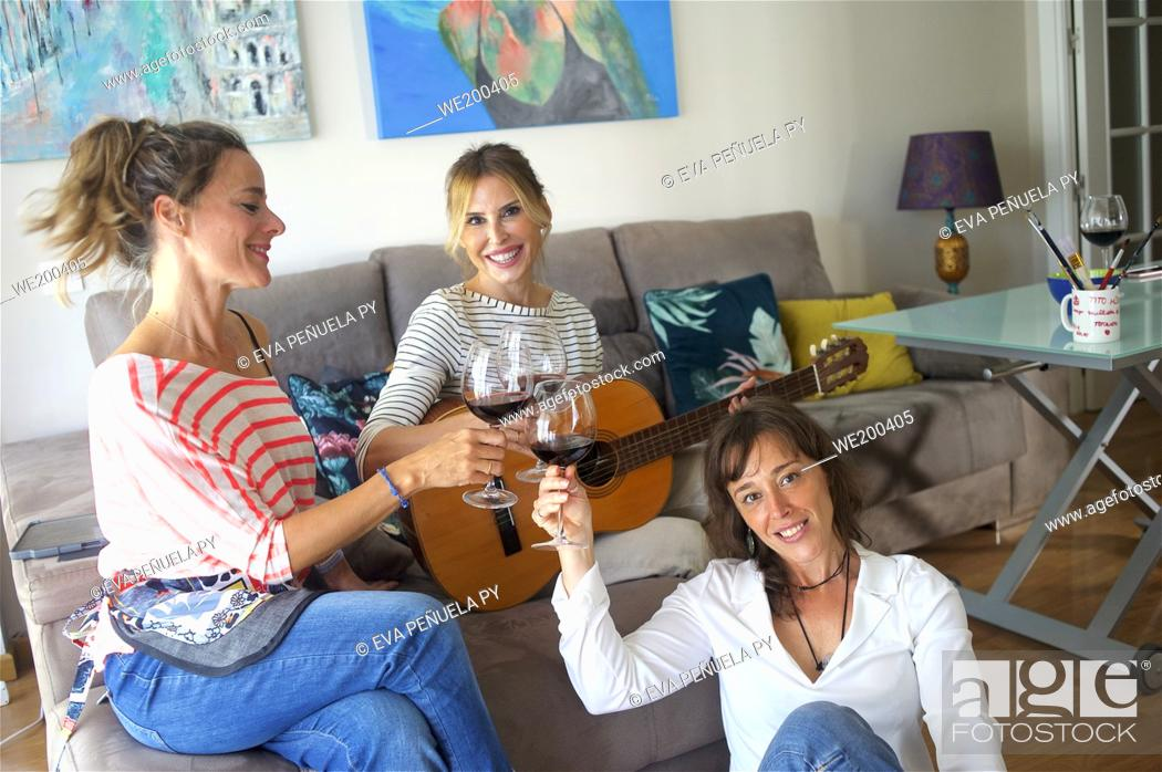 Photo de stock: Playing the guitar and toasting at a friends meeting.
