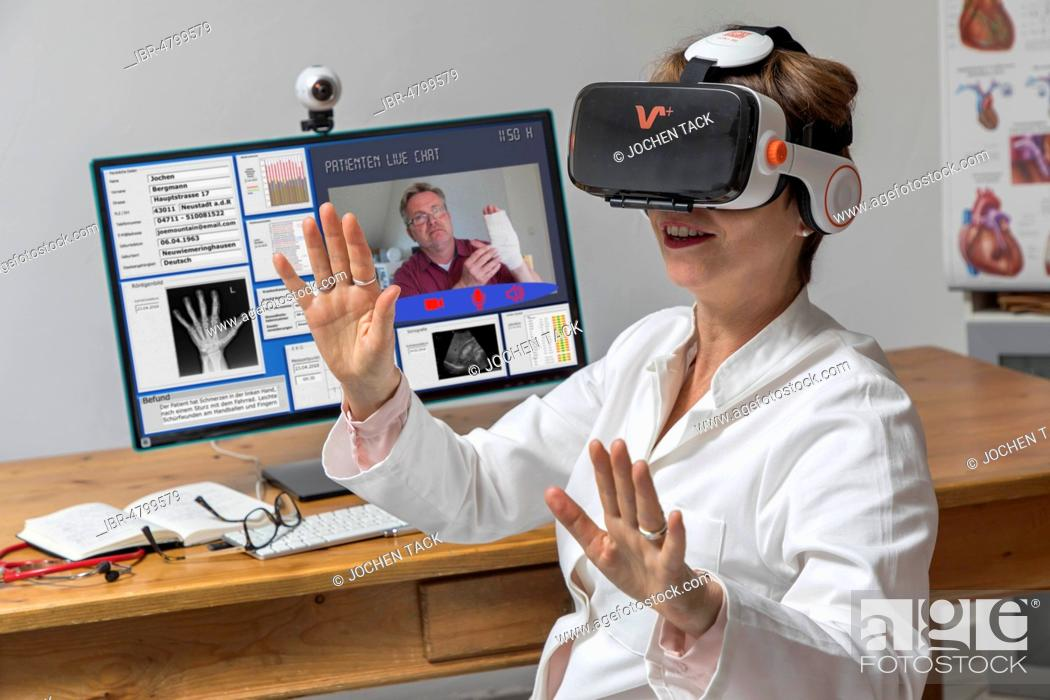 Stock Photo: Symbol photo for telemedicine, doctor in a practice, with VR glasses, Virtual Reality, 3-D presentation of an MRT result.