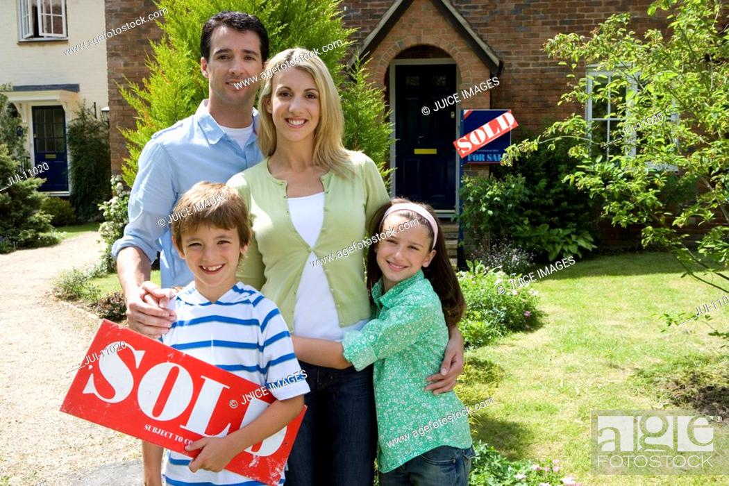 Stock Photo: Family of four outside house, boy 8-10 with 'sold' sign, smiling, portrait.