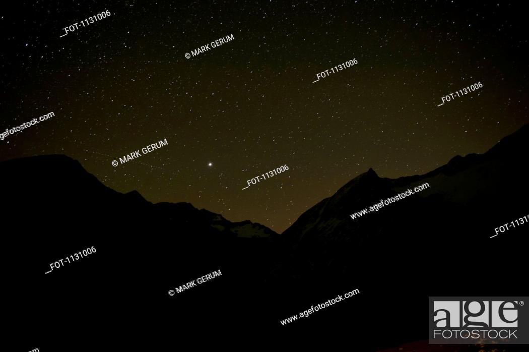 Stock Photo: A starry sky behind silhouetted mountains.