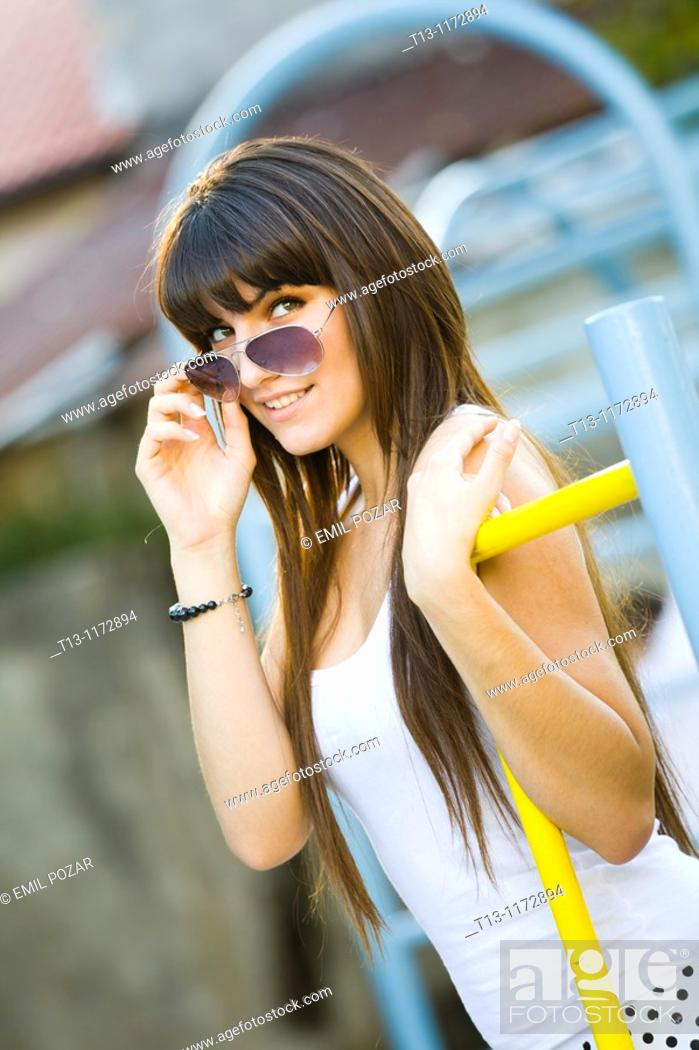 Stock Photo: Looking over sunglasses young woman on the playground.