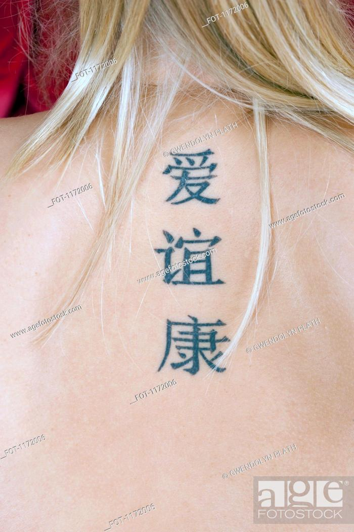 Stock Photo: A woman tattoos of Chinese characters meaning Love, Friendship and Health.