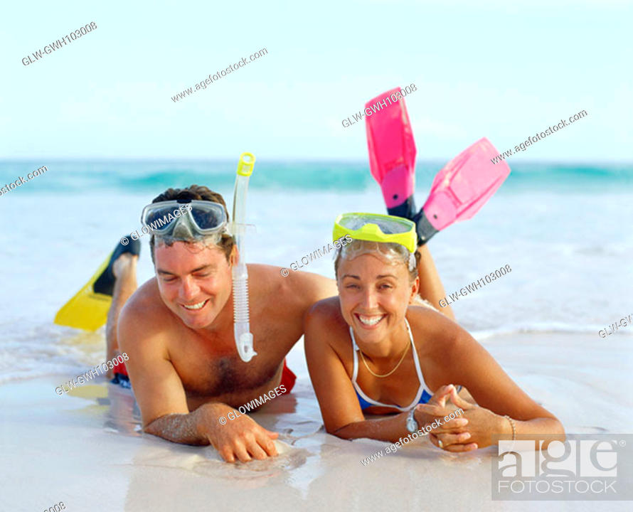 Stock Photo: Close-up of a young couple lying on the beach and wearing flippers, Bermuda.