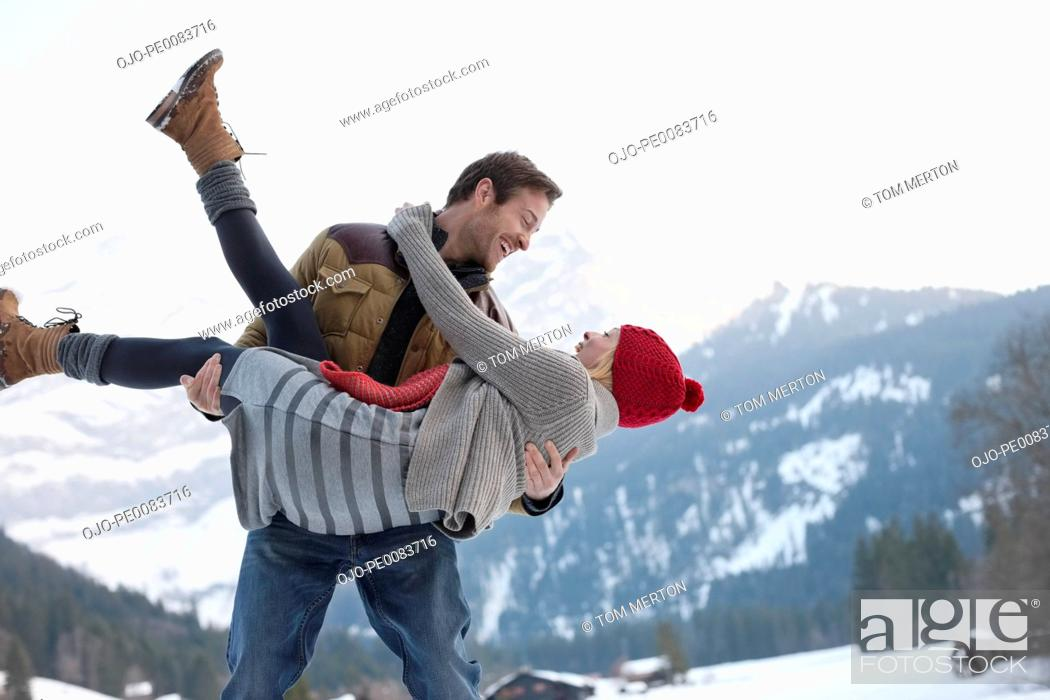 Stock Photo: Smiling man lifting woman in snowy field.