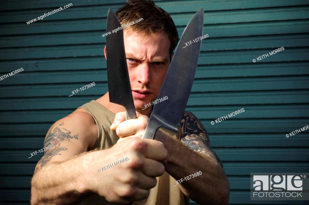 Stock Photo: Aggressive 30 year old man with knife.