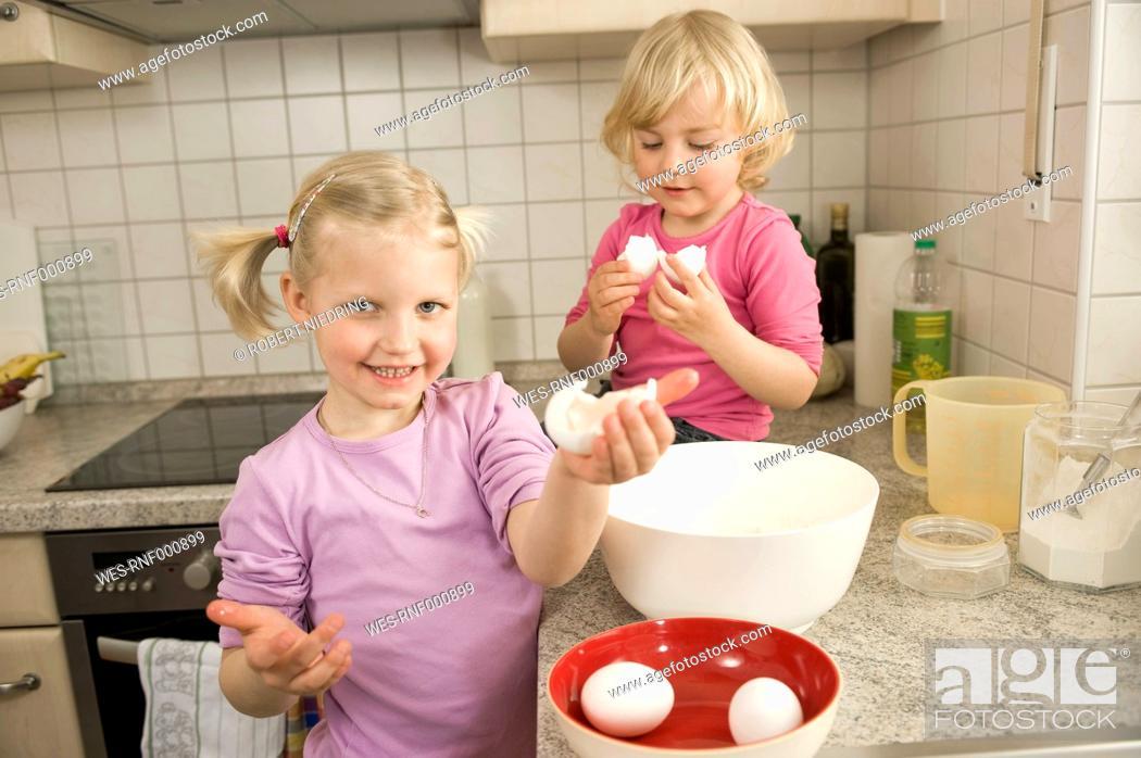 Stock Photo: Girls preparing cake in kitchen, smiling.