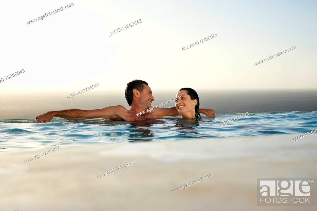 Stock Photo: Couple relaxing in infinity pool at sunset.