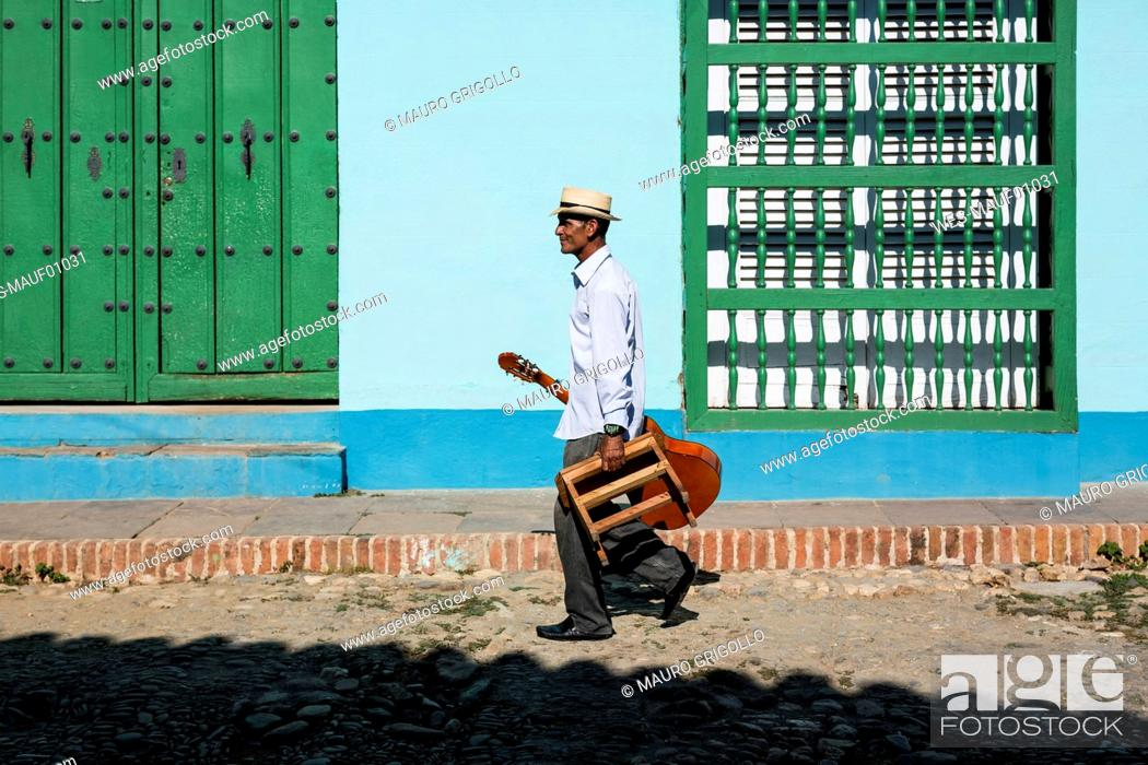 Stock Photo: Cuba, Trinidad, walking man with guitar and stool on the street.