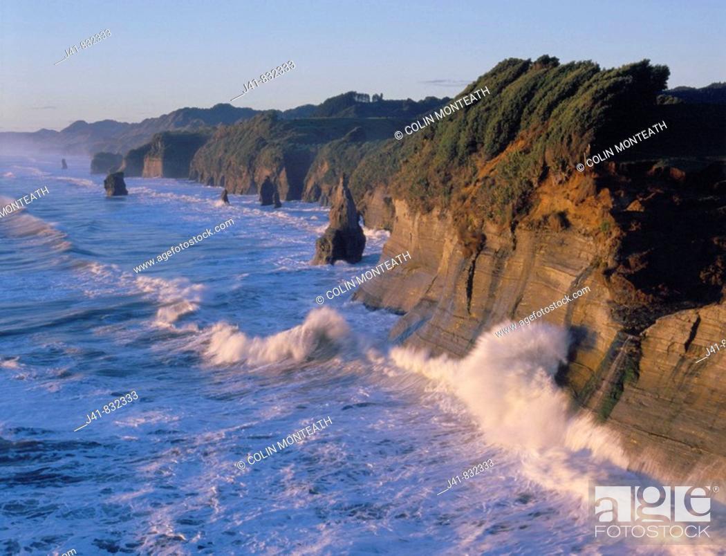 Stock Photo: Fertile coastal farmland ends abruptly in sandstone cliffs and stacks at Tongaporutu North Taranaki New Zealand.