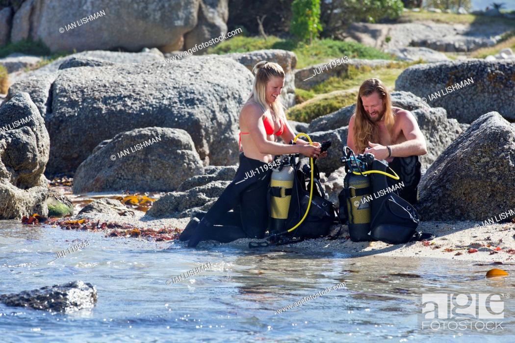 Stock Photo: Couple preparing scuba equipment for a dive from the beach.