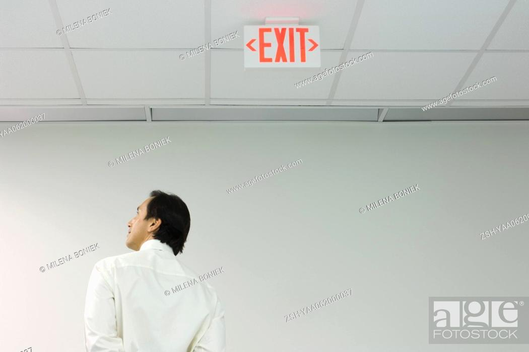 Stock Photo: Man standing below exit sign, looking away, rear view.