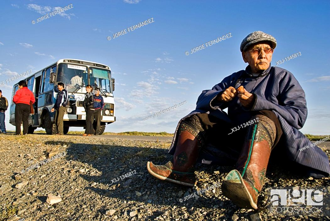 Stock Photo: Old Mongolian man, dressed in a traditional way, eating during a rest in a long bus ride, Mongolia.