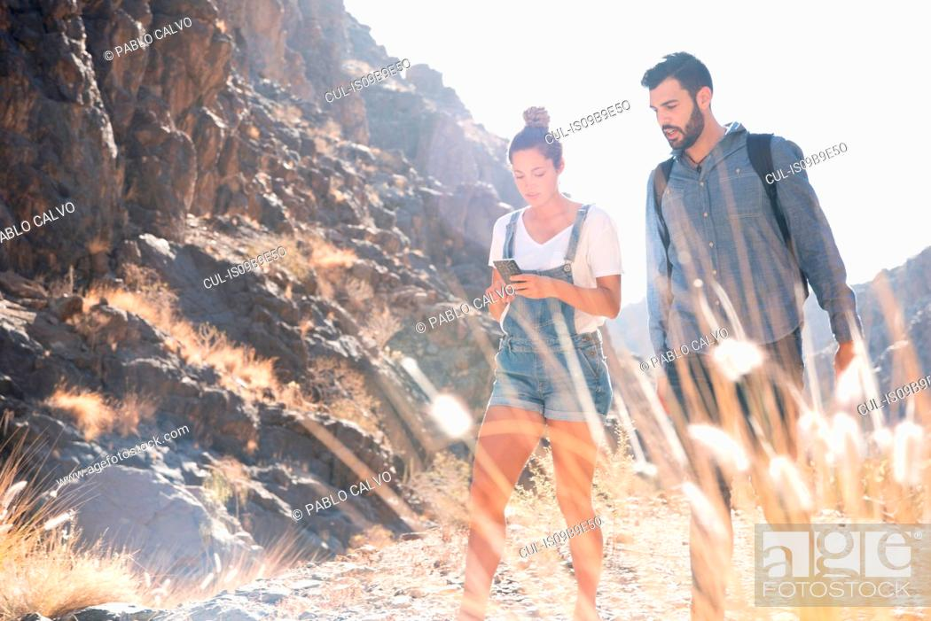 Stock Photo: Young hiking couple looking at smartphone while hiking in valley, Las Palmas, Canary Islands, Spain.