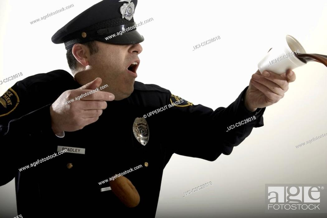 Stock Photo: Male police officer spilling his coffee.