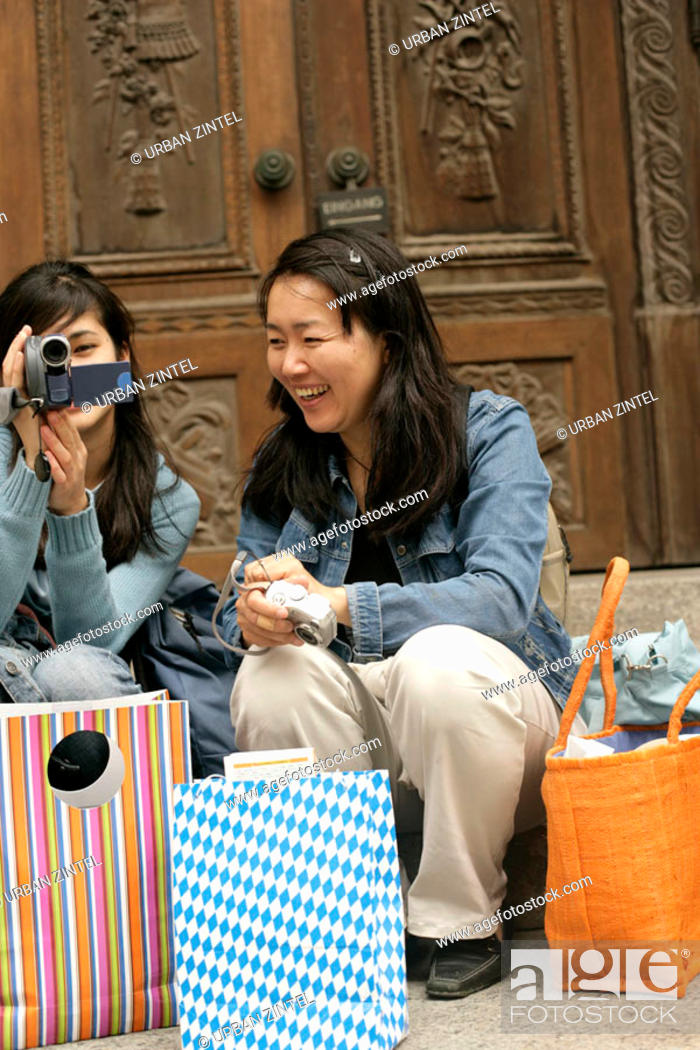 Stock Photo: Two young Asian women with shopping bags and cameras sitting in front of a wooden door of a church.