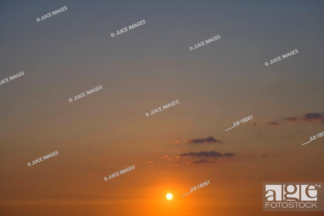 Stock Photo: Sun setting in sky.