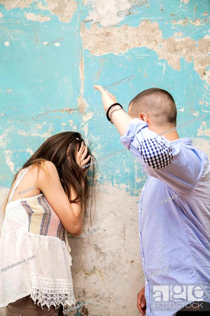 Photo de stock: Man beating up his wife illustrating domestic violence.