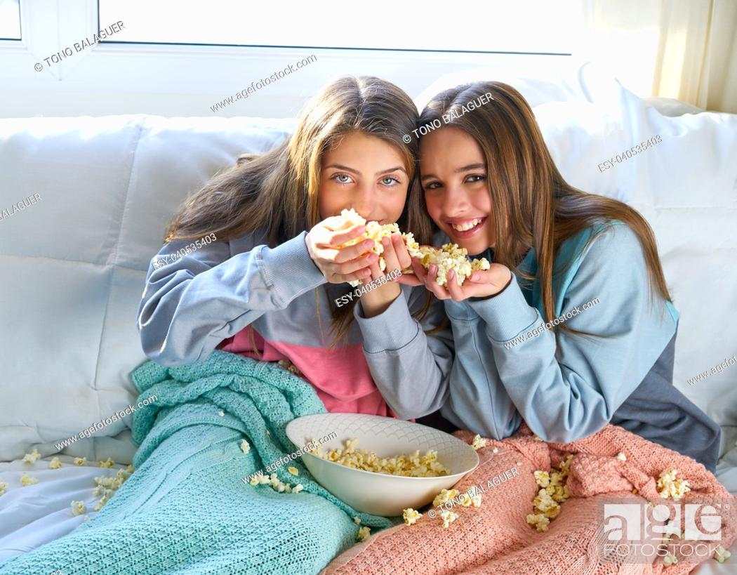 Stock Photo: best friend girls at sofa having fun with popcorn watching movie.