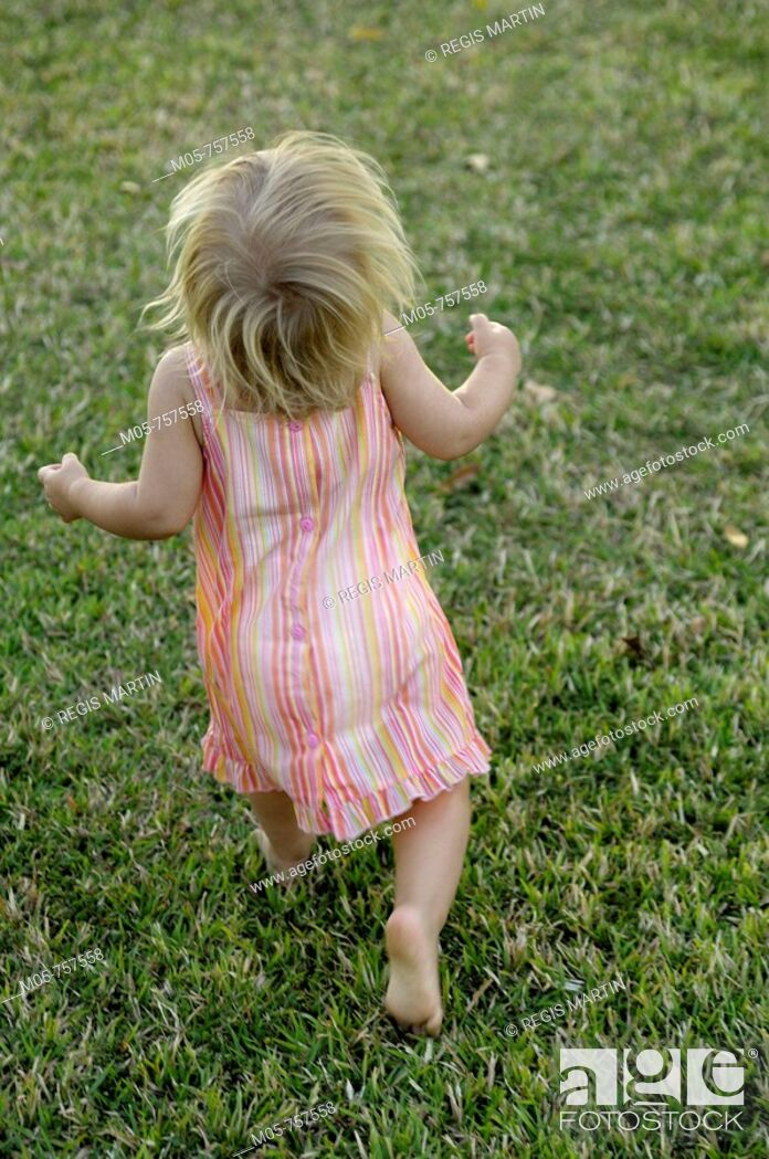 Stock Photo: 16 months old toddler running in the grass.