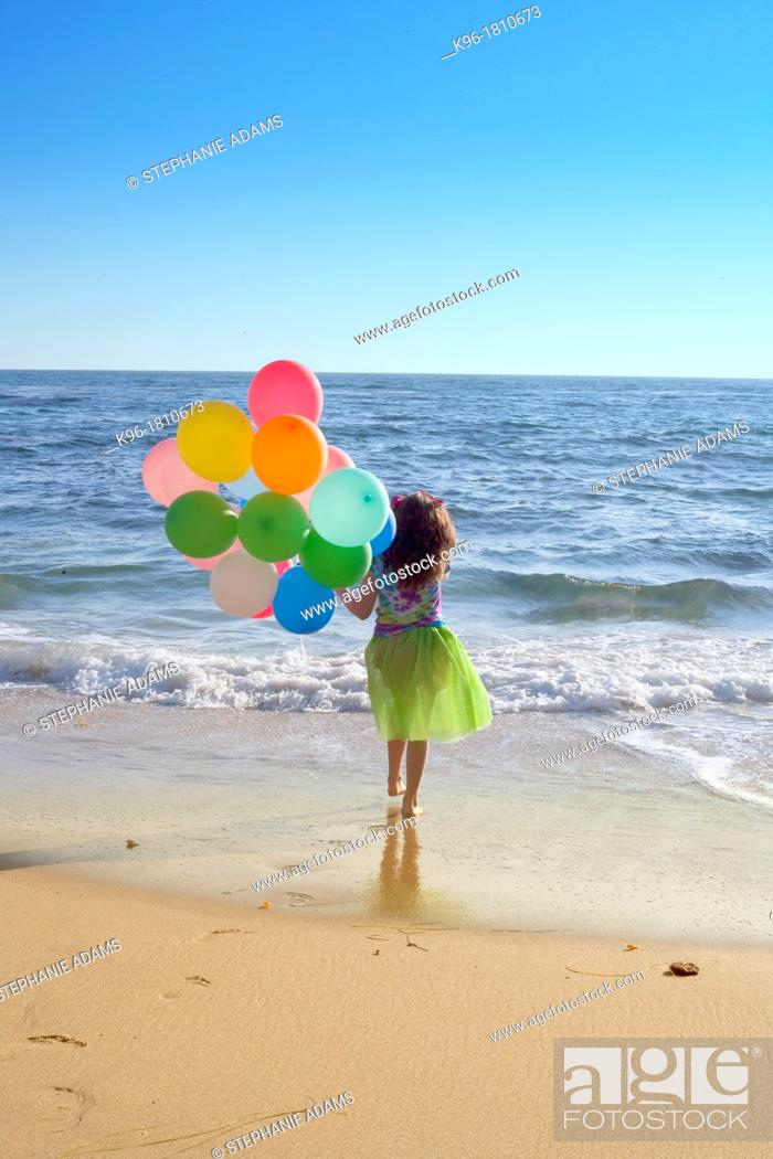Stock Photo: young girl walking towards the ocean with balloons with a view to see forever.