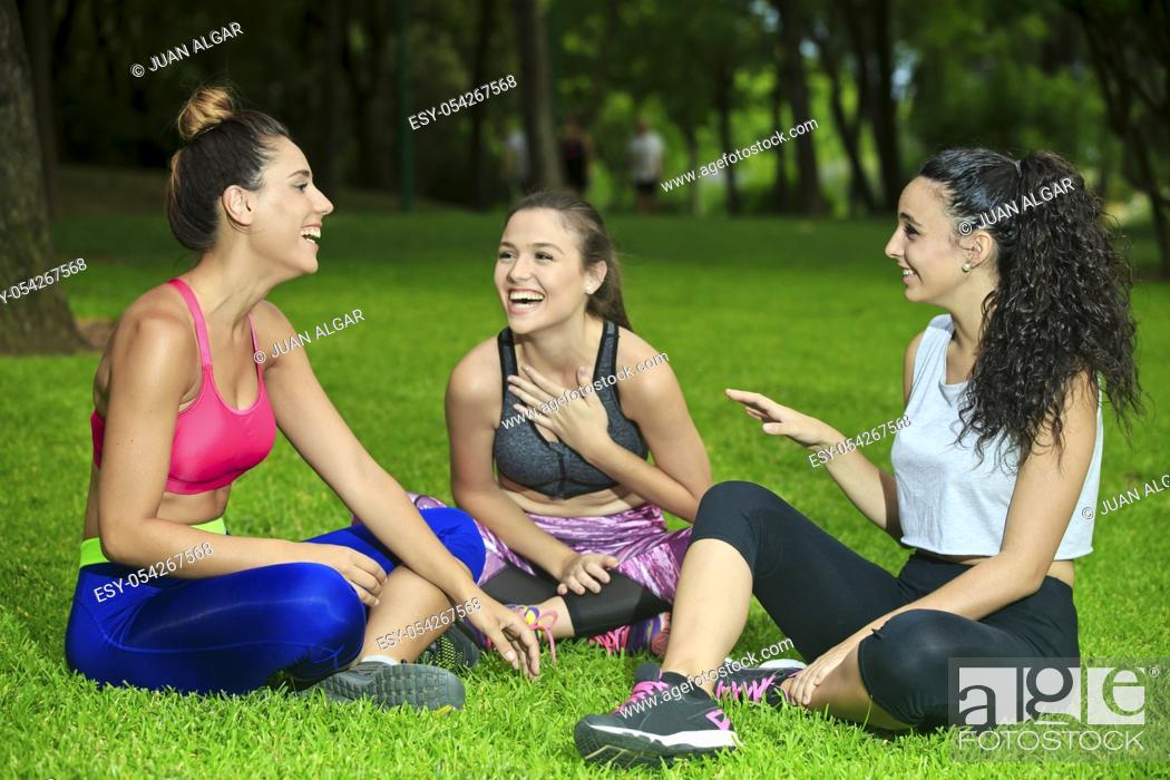 Stock Photo: Leg crossed laughing friends having fun after training in park.