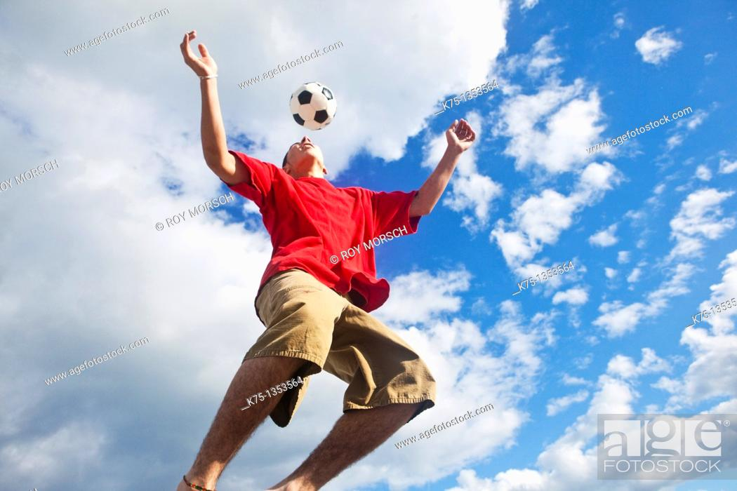 Stock Photo: teen hits soccer ball high in the sky.