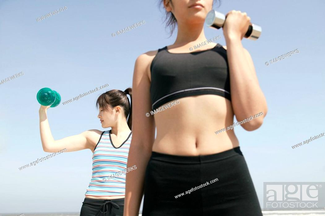 Stock Photo: Two women hold dumbbells under the sky.