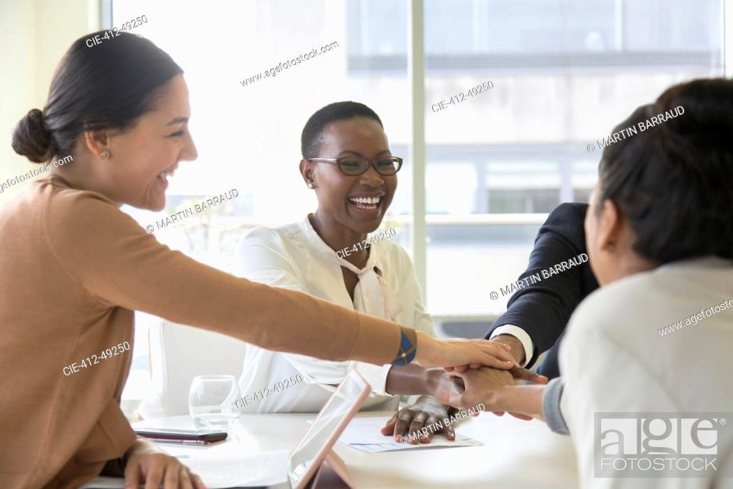 Stock Photo: Happy business people joining hands in conference room meeting.