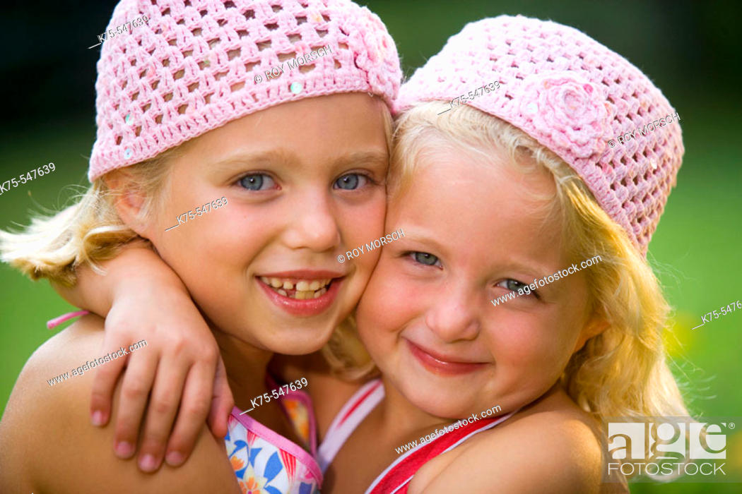Imagen: Caucasian blonde sisters hugging and smiling.