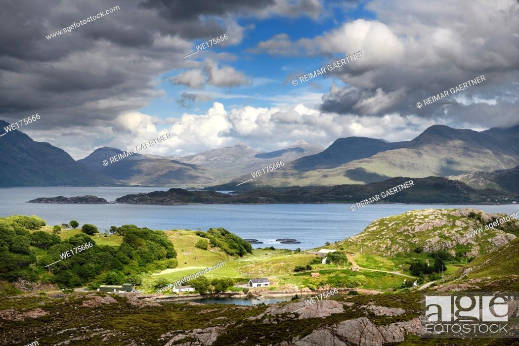 Stock Photo: Sun on Ardheslaig village on Loch Beag and fish farm on Loch Shieldaig and Torridon Hills at Upper Loch Torridon Scottish Highlands Scotland.