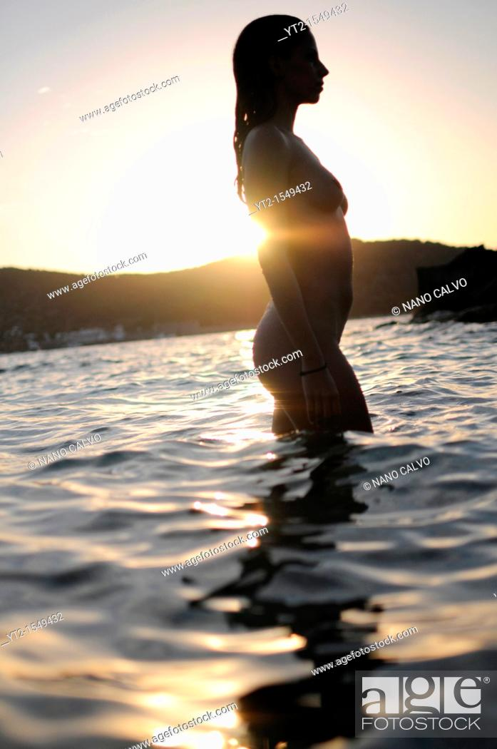 Stock Photo: Young attractive woman relaxing at sunset, in the Mediterranean Sea waters.