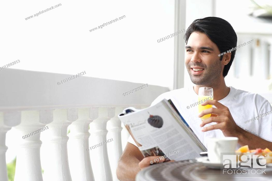 Stock Photo: Young man having breakfast and reading magazine.