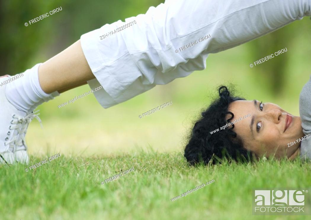 Stock Photo: Young woman doing plow pose outdoors, smiling at camera.