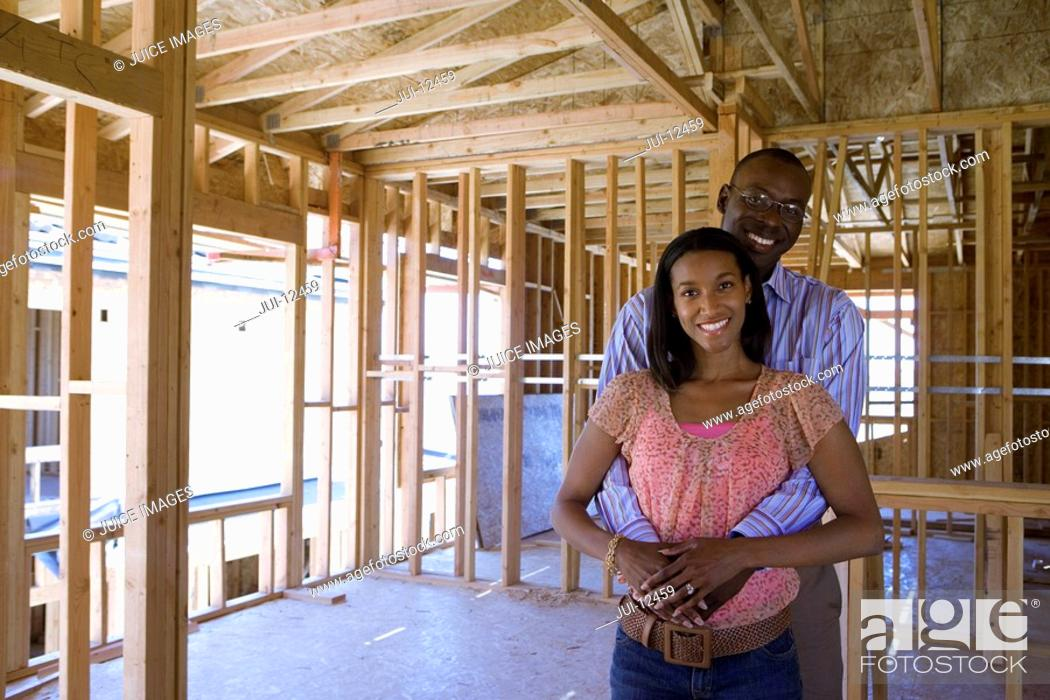 Stock Photo: Young couple in partially built house, man embracing woman, smiling, portrait.