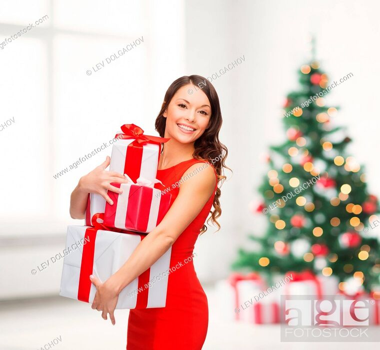 Stock Photo: christmas, x-mas, valentine's day, celebration concept - smiling woman in red dress with many gift boxes.