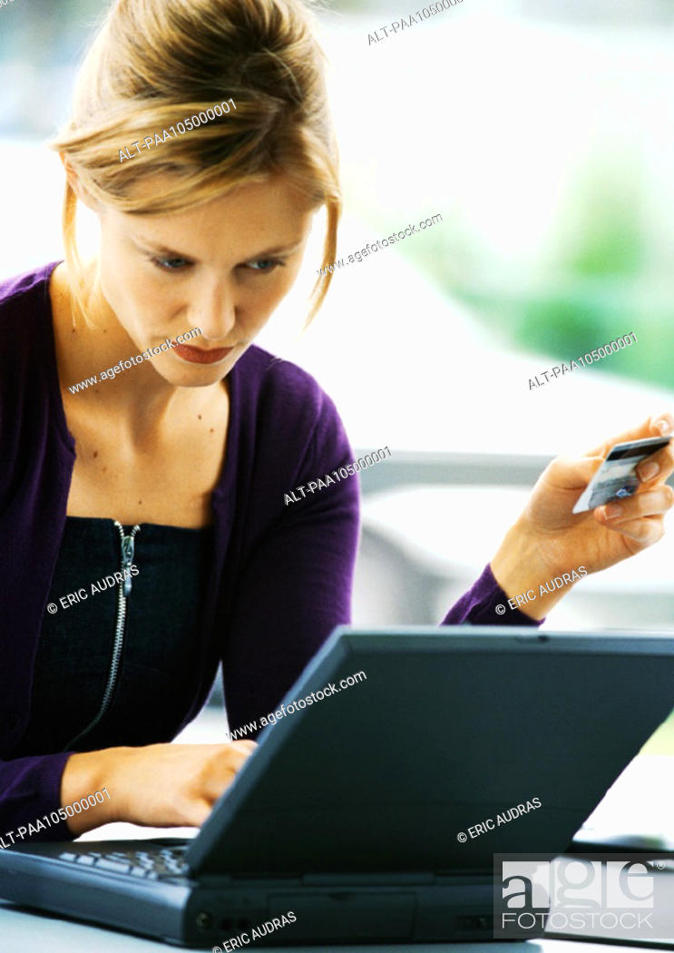 Stock Photo: Woman using laptop computer and holding credit card.