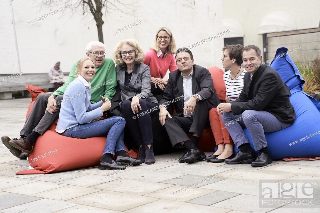 Stock Photo: Group of friends sitting on large cushions outdoors.