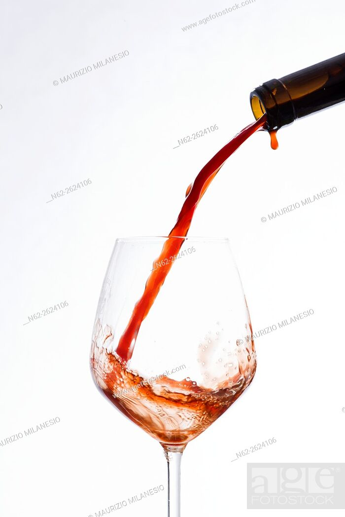 Stock Photo: Wine poured from a bottle into a wine glass, on a white background.