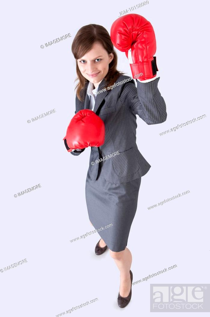 Stock Photo: Businesswoman looking up and wearing boxing glove with smile.