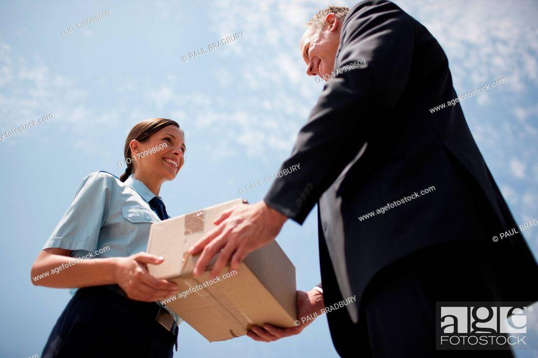 Stock Photo: Supervisor handing box to worker.