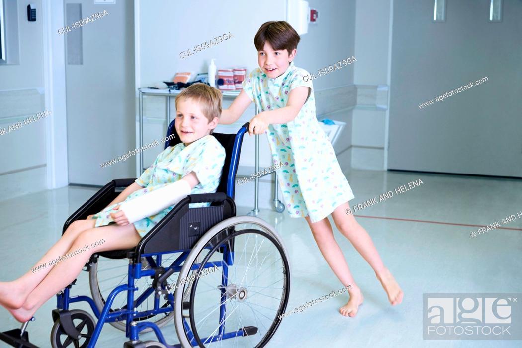 Stock Photo: Boy patients pushing friend in wheelchair on hospital children's ward.
