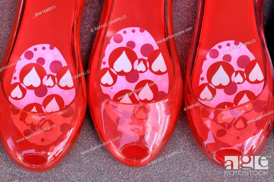 Stock Photo: Red plastic shoes for sale.