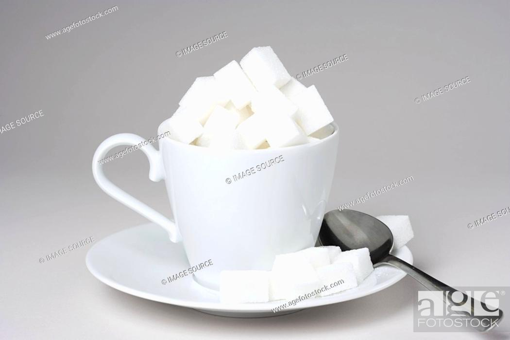 Stock Photo: A cup full of sugar lumps.