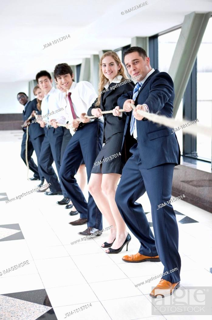 Stock Photo: Business people standing in a row and playing tug-of war.