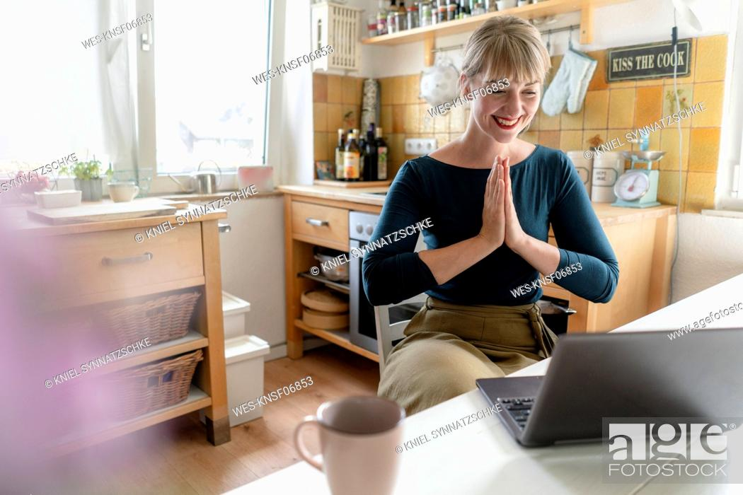 Stock Photo: Portrait of laughing woman with laptop practicing yoga in the kitchen.