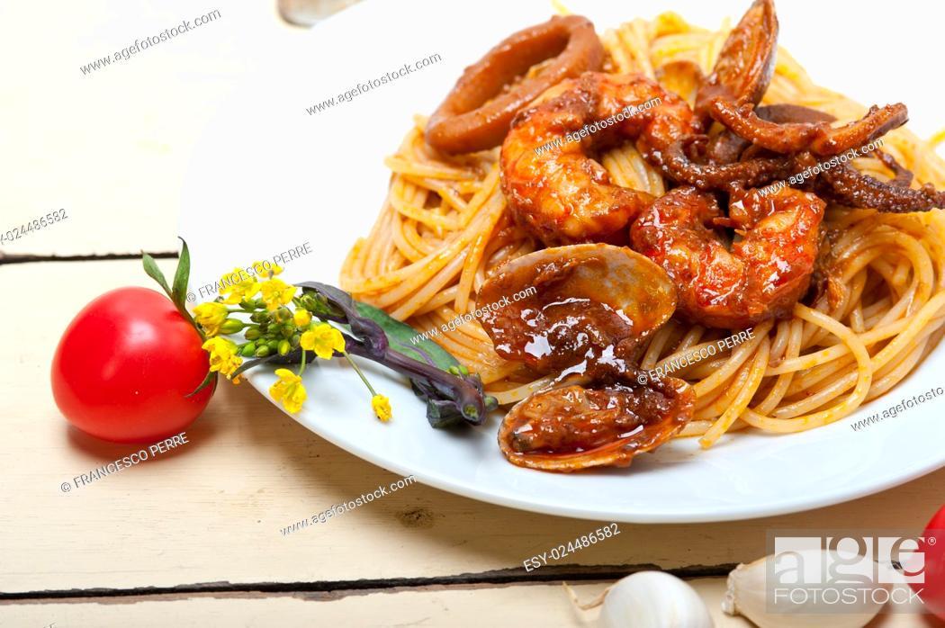 Stock Photo: Italian seafood spaghetti pasta on red tomato sauce over white rustic wood table.