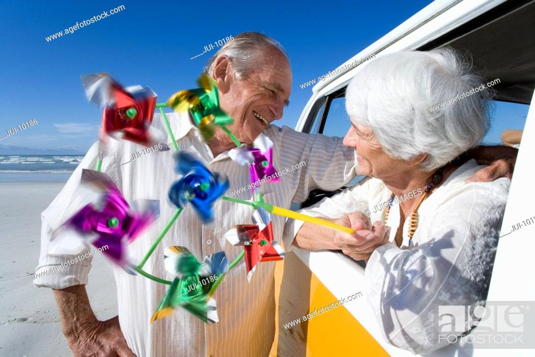 Stock Photo: Senior man embracing woman with pinwheel through window of camper van on beach, smiling.