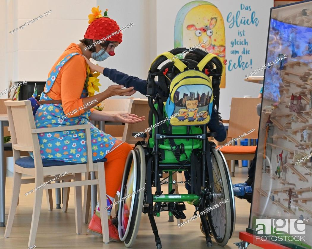 Stock Photo: 19 August 2021, Brandenburg, Burg: The clown Pepina Peppich from Lachen hilft e.V. takes care of a child in a wheelchair at the children's hospice.
