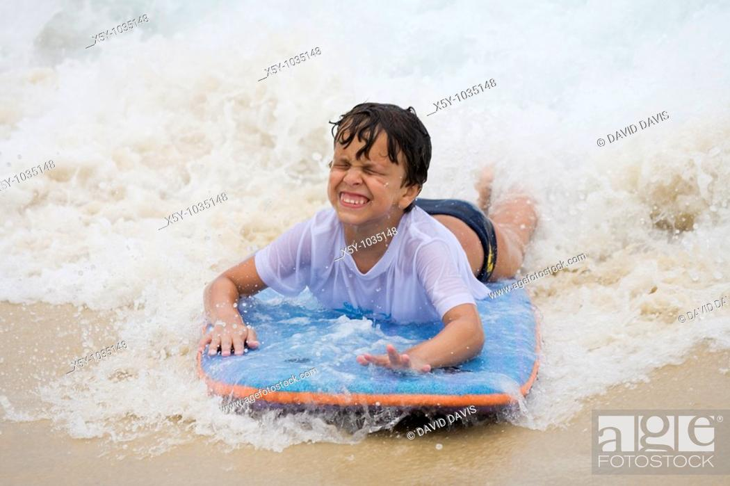 Stock Photo: Young Brazilian boy playing on surf board on Copacabana Beach in Rio de Janeiro in Brazil.