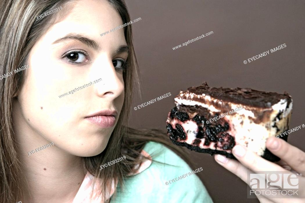 Stock Photo: Portrait of a teenage girl holding a piece of cake.